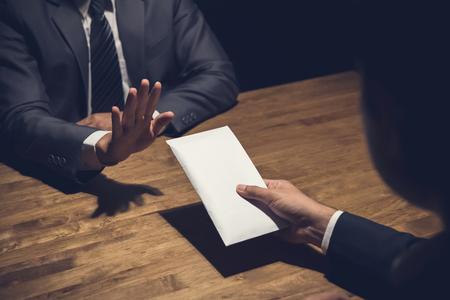 Der Geschäftsmann, der Geld im weißen Umschlag zurückweist, bot von seinem Partner in der Dunkelheit an - Bestechungsgeldkonzept