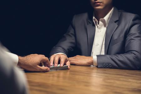 Nieuczciwy biznesmen potajemnie dając pieniądze swojemu partnerowi w ciemności - przekupstwo, przekręt i koncepcje venality
