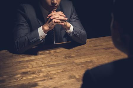 Detective che intervista il sospetto in camera oscura - concetti di indagine e interrogatorio
