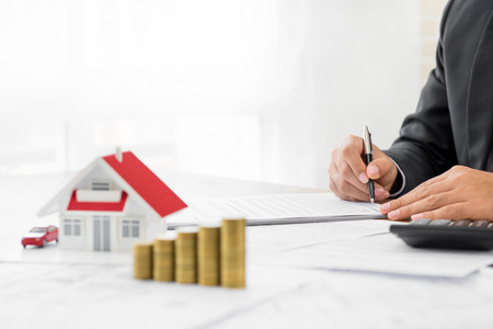 Businessman signing document with money and house model on the table - real estate and properties financial concepts Stockfoto