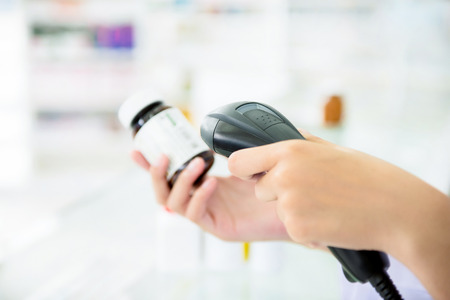 Pharmacist scanning medicine bottle with barcode scanner in pharmacy