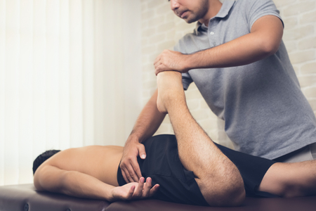 Physical therapist stretching leg of sportsman patient in clinic Stock Photo