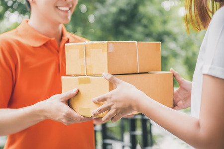 Smiling delivery man in orange uniform delivering parcel box to a woman customer - courier service concept