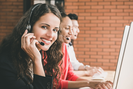 아름 다운 여자 텔 레 마케팅 고객 서비스 에이전트 그녀의 다민족적인 팀과 콜 센터 사무실에서 일하고 웃 고