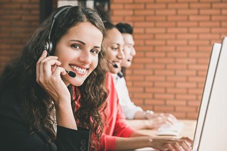 Agent de service à la clientèle de télémarketing belle femme souriante travaillant dans le bureau du centre d'appel avec son équipe multiethnique Banque d'images