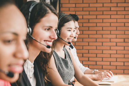 Smiling multiethnic telemarketing customer service agent team working in call center office with healpful attutude
