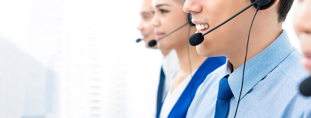 Call center agents talking on the phone to customers with a friendly and helpful attitude - panoramic banner with copy space 版權商用圖片 - 113993948