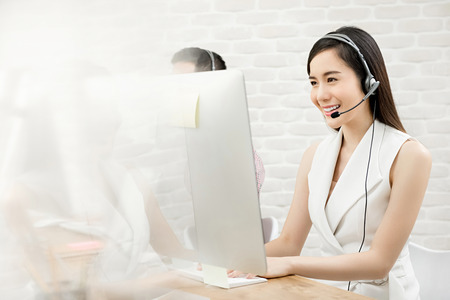 Smiling beautiful Asian woman telemarketing customer service agent working in call center office