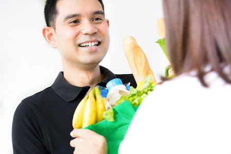 Asian grocery store delivey man wearing an black polo-shirt delivering food to a woman at home