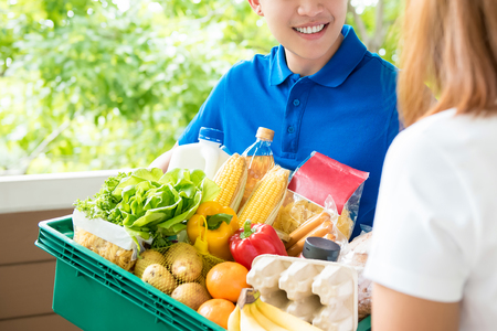 Grocery store delivery man wearing a blue polo-shirt delivering food to a woman at home