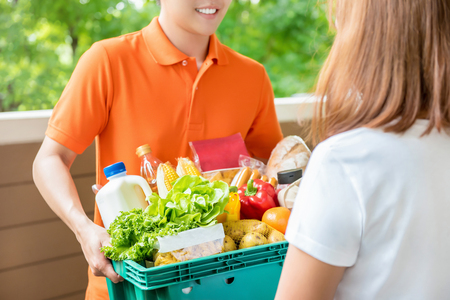 Grocery store delivery man wearing an orange polo-shirt delivering food to a woman at home