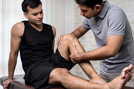 Therapist treating injured knee of handsome athlete male patient - sport physical therapy concept