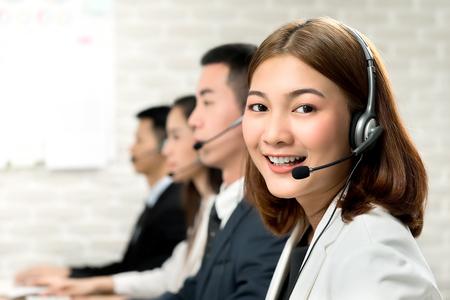 Lächelnde schöne junge Asiatin, die im Callcenter-Büro mit freundlicher und hilfsbereiter Einstellung arbeitet
