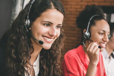 Glimlachende mooie jonge de dienstagent van de vrouwentelemarketingservice die in call centrebureau werken met vriendschappelijke en nuttige houding