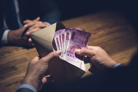 Businessman counting money, Indian Rupee currency, in the envelope just given by his partner after making an agreement in private dark room - loan, briberry and corruption scam concepts Standard-Bild