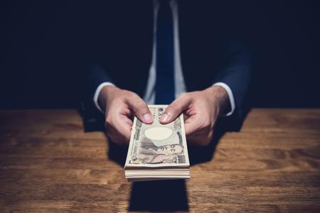 Hombre de negocios anónimo secretamente regalando dinero, moneda del yen japonés, en habitación oscura privada - conceptos de préstamo, estafa y soborno