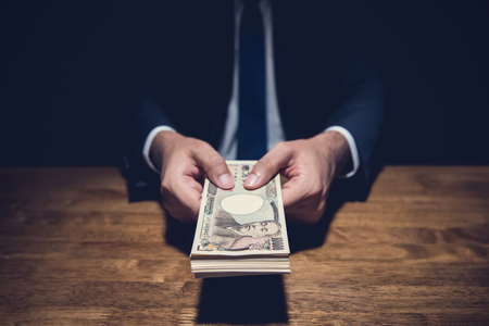 Anonymous businessman secretly giving away money, Japanese Yen currency, in private dark room - loan, scam and bribery concepts