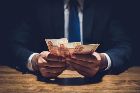 Geschäftsmann, der Geld, Währung des russischen Rubels, am Tisch im dunklen privaten Raum - Sterblichkeits- und Korruptionskonzepte zählt
