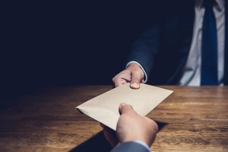 Ein Mann, der einem anderen Geschäftsmann in einem Korruptionsstrug Bestechungsgeld in einem braunen Umschlag gibt