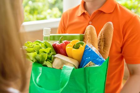 W sklepie spożywczym mężczyzna ubrany w pomarańczową koszulkę polo dostarcza jedzenie kobiecie w domu