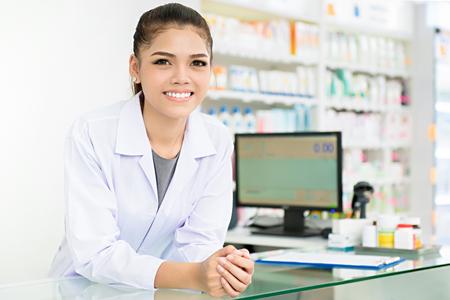 Lächelnder schöner junger Asiatinapotheker im weißen Kleidermantel am Zähler in der Apotheke (Drogerie oder Drogerie) Standard-Bild