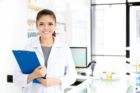 Smiling beautiful young Asian woman pharmacist in white gown coat at working in pharmacy (chemist shop or drugstore)