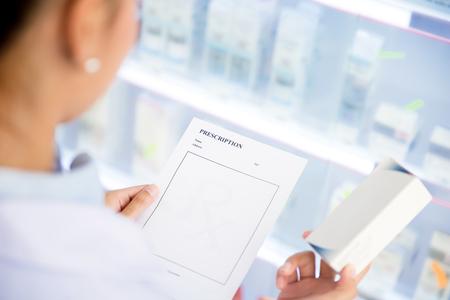 Female doctor or  pharmacist holding Rx prescription paper checking medicine in pharmacy (or chemist shop)