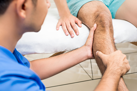 Doctor (therapist) treating male patient leg while sitting on the bed in clinic - physical therapy concept