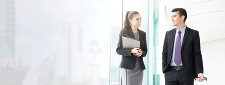 Asian businesswoman talking with a male colleague while walking in the building corridor (or airport terminal ) - panoramic web banner with copy space