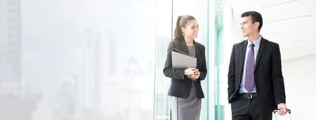 Mulher de negócios asiático falando com um colega masculino enquanto caminhava no corredor do edifício (ou terminal de aeroporto) - banner web panorâmica com espaço de cópia