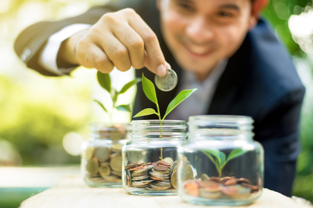 Businessman putting coin into the glass jar with young plant, demonstrating financial growth through saving plans and investment schemes Reklamní fotografie