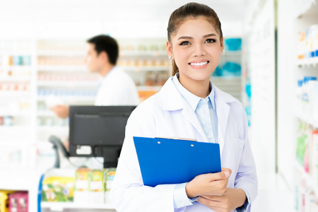 Beautiful Asian female pharmacist working in a pharmacy (or drugstore)  with her colleague. Stock Photo