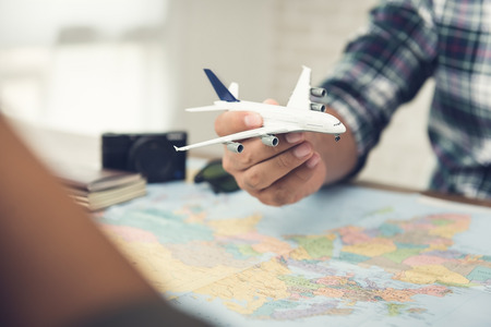 A man holding a plane model over a world map while planning holiday travel aboard for him and his partner to their dream destinations