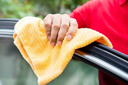 valeting: Male auto care service staff cleaning car window with microfiber cloth Stock Photo