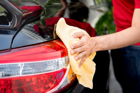 valeting: Male auto care service staff cleaning car tail light with microfiber cloth
