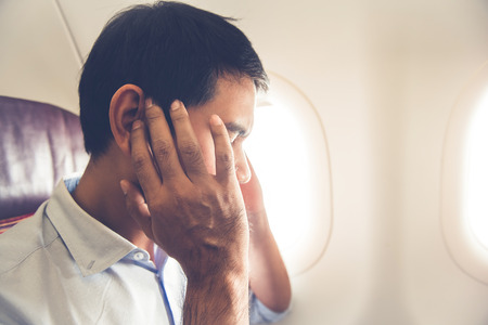 Male passenger having ear pop on the airplane while taking off (or landing) Stockfoto