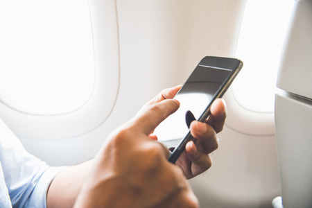 Male passenger using mobile phone on the airplane while traveling