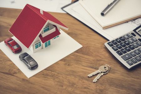House model, key and calculator with documents on the table - real estate and property concept Banque d'images