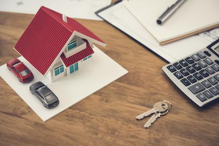 Modelo de casa, llave y calculadora con documentos sobre la mesa - bienes raíces y concepto de propiedad
