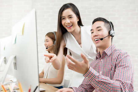 Female Asian supervisor discussing work with telemarketing customer service agent team in call center Фото со стока