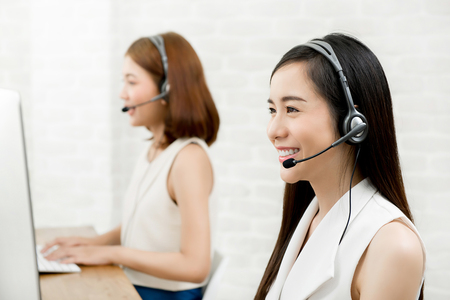 Smiling Asian woman telemarketing customer service agent team, call center job concept