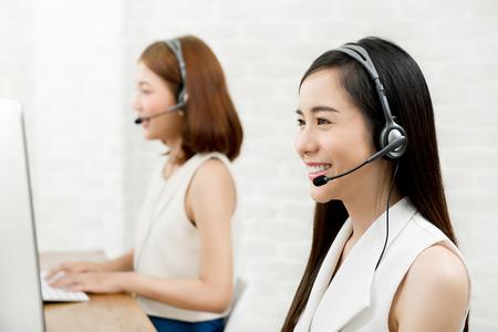 Smiling Asian woman telemarketing customer service agent team, call center job concept