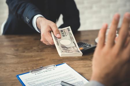 Uomo d'affari che rifiuta denaro, banconote in yen giapponesi, offerte dal suo partner mentre stipula un contratto - concetto anti corruzione Archivio Fotografico - 92770274
