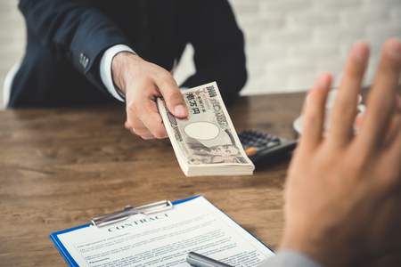 Businessman rejecting money, Japenese yen banknotes,  offered by his partner while making contract - anti bribery concept Stockfoto