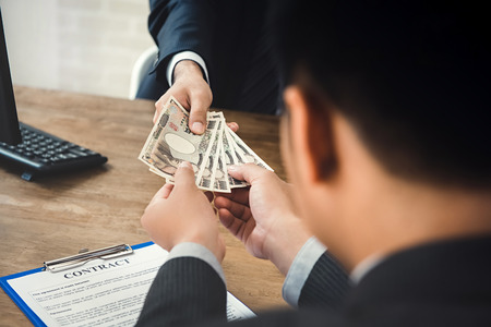 Businessman giving money, Japanese yen currency, to his partner while making contract