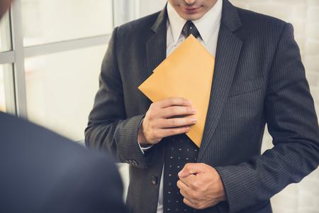 スーツのポケットに封筒を入れるビジネスマン - 汚職と横領の概念