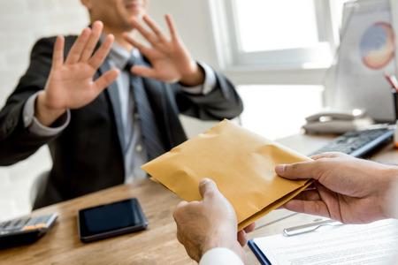 Empresario que rechaza el dinero en el sobre ofrecido por su compañero - concepto anti soborno