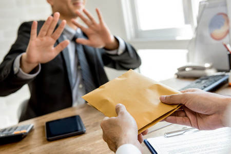 Businessman rejecting money in the envelope offered by his partner - anti bribery concept Standard-Bild