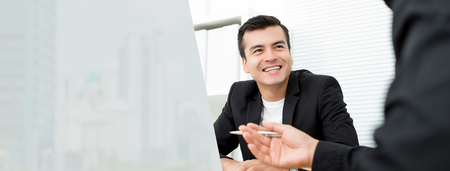 Happy businessman discussing work with his colleagues at the meeting in the office - panoramic web banner with copy space