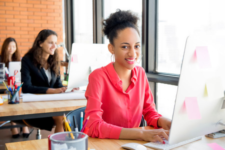Smiling beautiful black businesswoman at working desk in creative office with her female colleagues in background